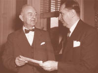 On September 9, 1947, FDIC Chairman Maple Harl (right) presented to Under Secretary of the Treasury A.L.M. Wiggins a check for $146 million, repaying more than half of the government's initial funding of the FDIC.  The balance was repaid in 1948.