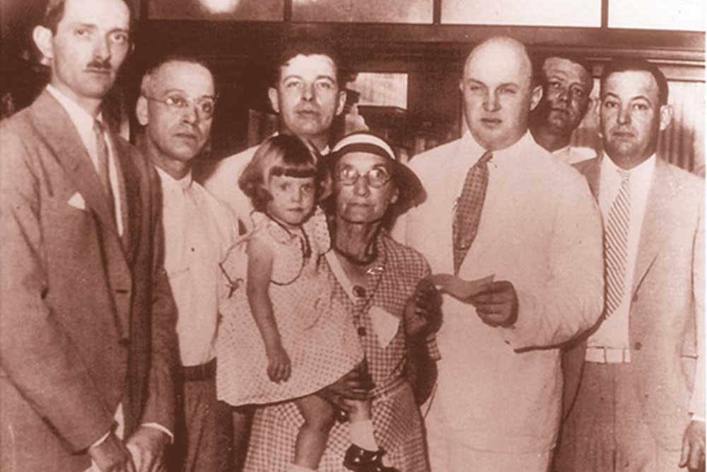 On July 5, 1934, Mrs. Lydia Lobsiger received the first federal deposit insurance disbursement, following the failure of the Fond Du Lac State Bank in East Peoria, Illinois. Photo: UPI
