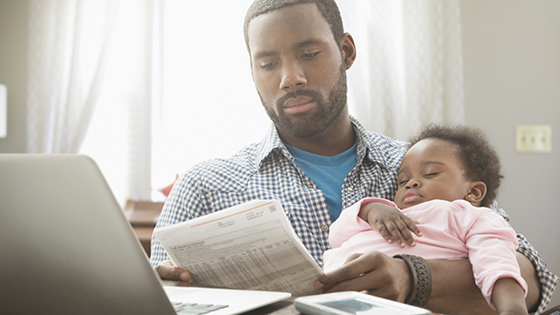 July Article Monthly Image - a young father holding his baby girl in his arms, while reviewing his bills
