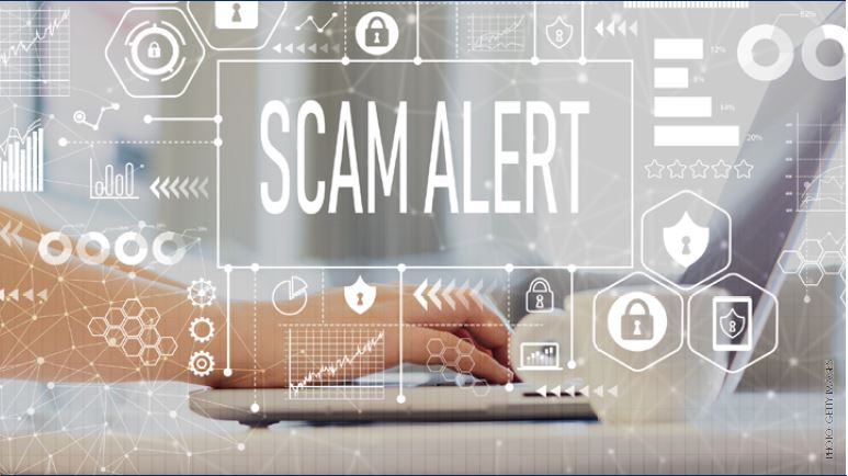 October Article Monthly Image of hands typing and Scam Alert with warning signs floating all over