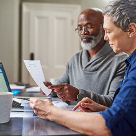 Picture of couple completing forms- consumer assisitance webpage includes useful information to help you make informed decisions about your money and to protect yourself against financial scams and fraud.